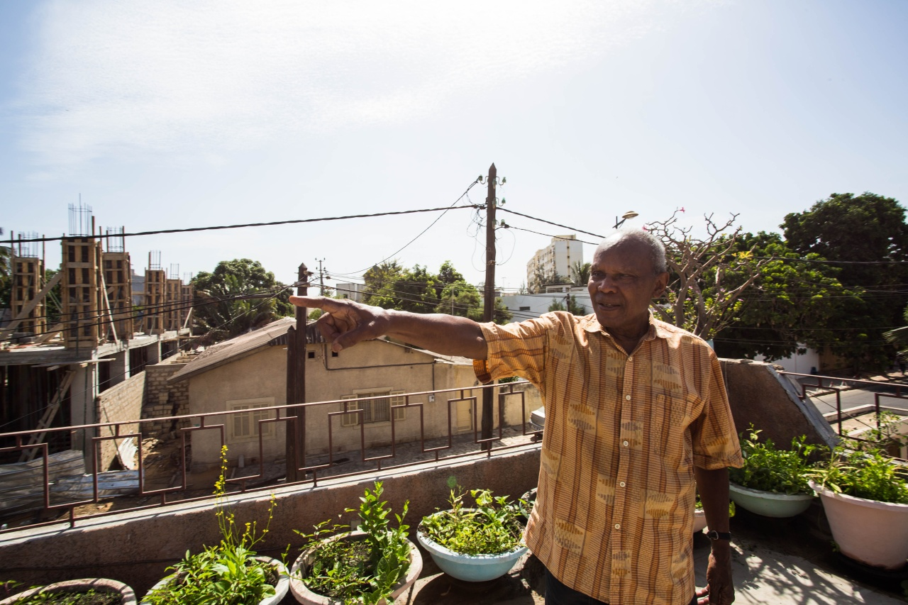 Jean Gomis point to the view from his rooftop in Dakar, where he keeps a collection of Vietnamese herbs.