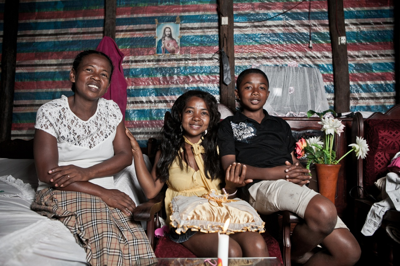 Nirina (center), a vanilla worker in Sambava, poses at home with her mother and her son.