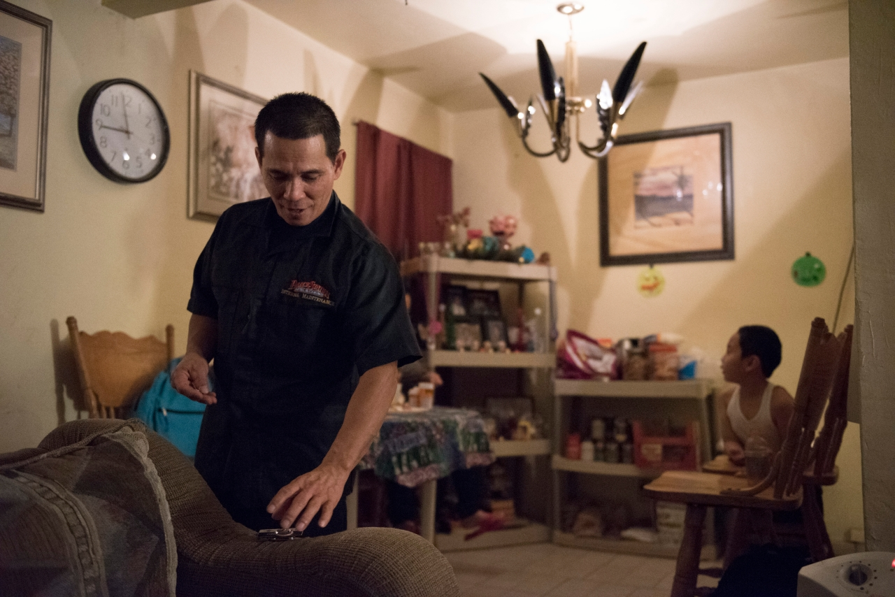 At his Las Vegas home, Casiano Corpus Jr. prepares to put the name tag on his uniform before leaving to work a graveyard shift.
