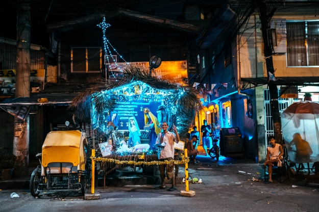 "1. A man poses in front of a ""Belen,"" a creche representing the Nativity scene, in the streets of Manila. / 2. Millions of people visit the Recto-Divisoria night markets during the holiday season."