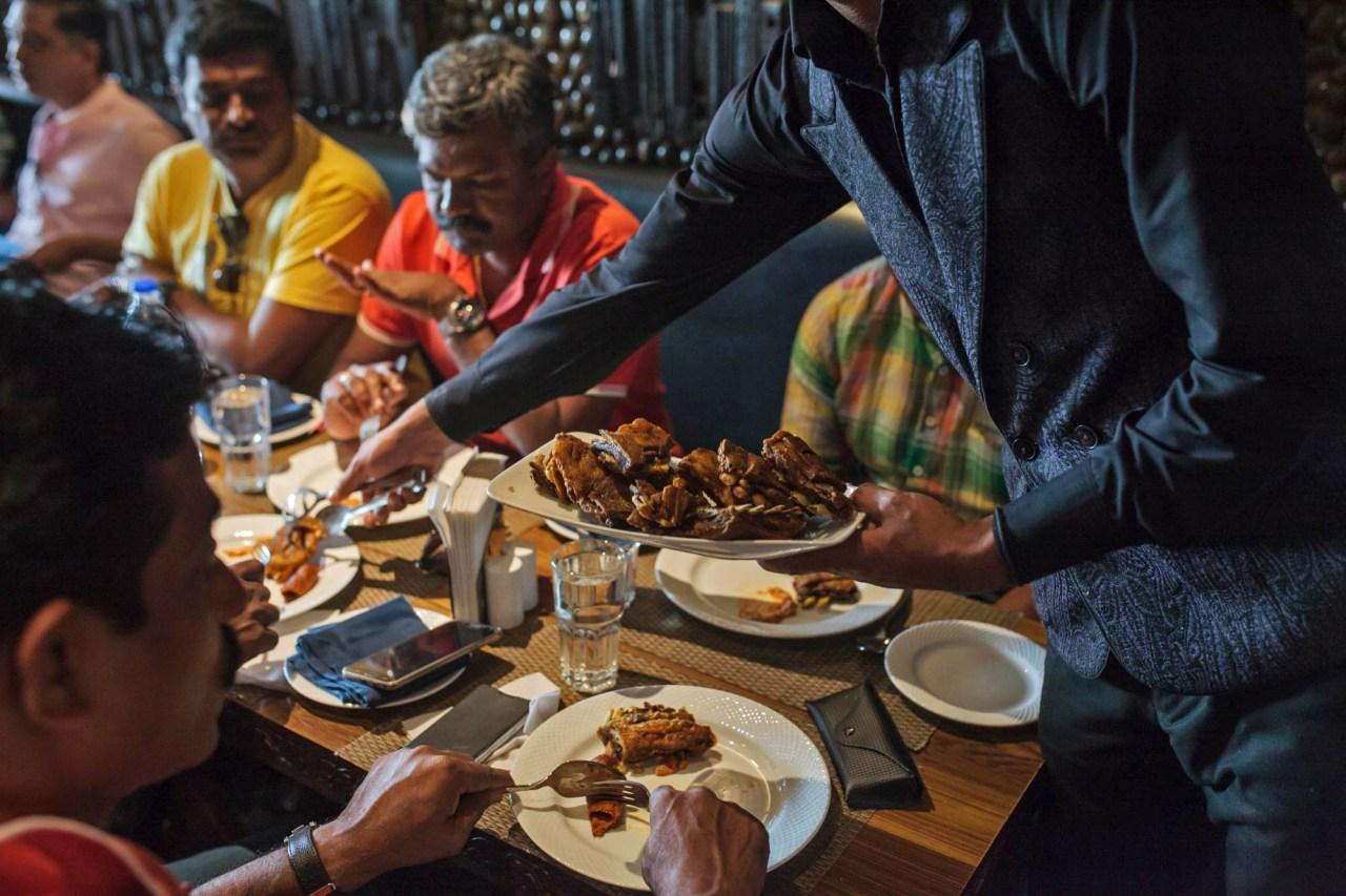 An employee of Ahdoo's Hotel serves a traditional Kashmiri dish to Hindu tourists.