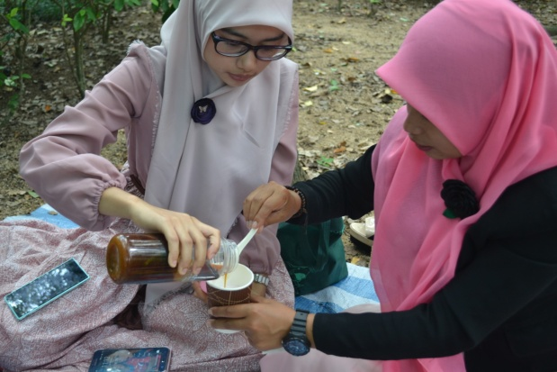 Indonesian women carefully pour palm sugar into a cup of ice and coconut milk, making cendol.