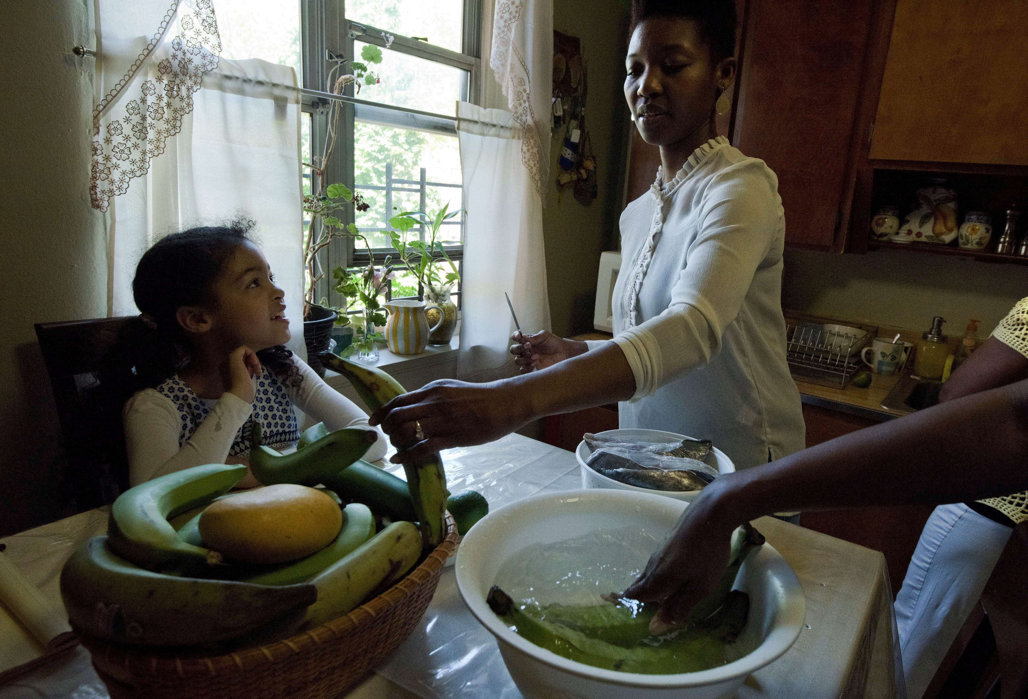 Sara Martinez's daughter, Isha Sumner, prepares the plantains.