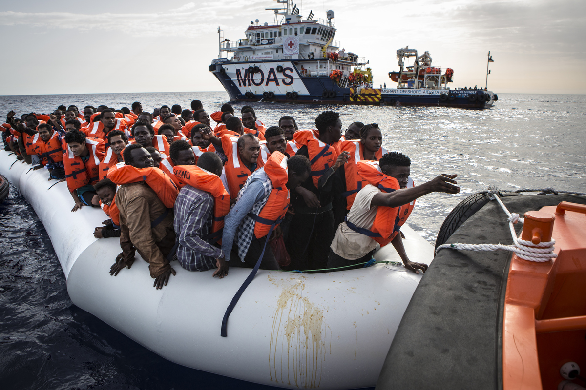 Migrants on a rubber boat transfer to a faster rescue craft.