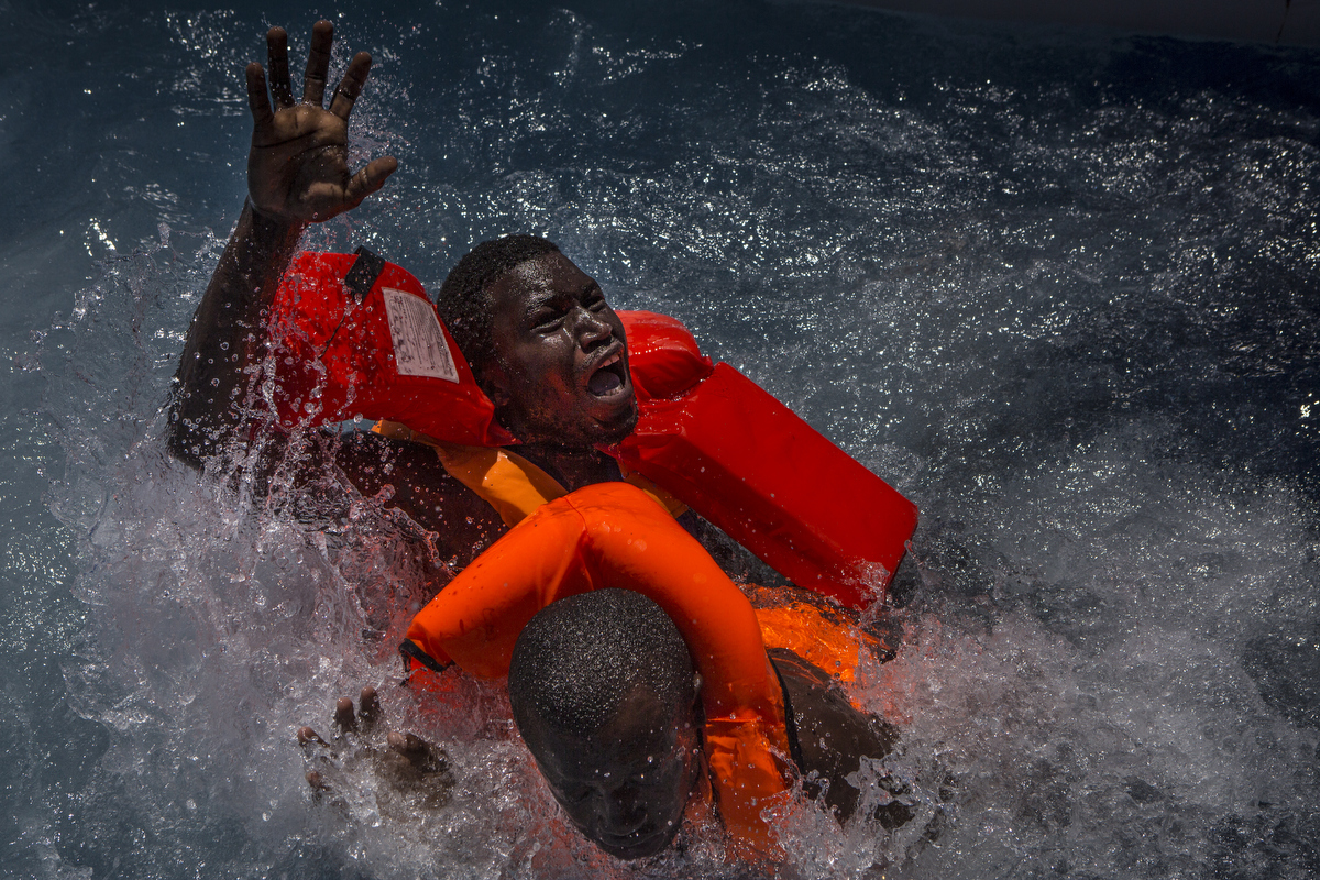 Two men panic after their rubber boat deflated, tipping many migrants into the water.