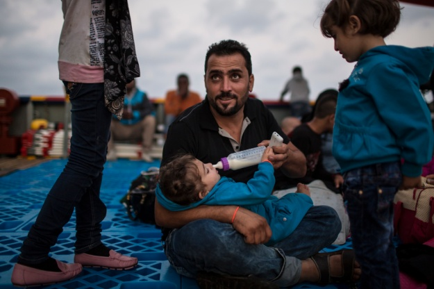 1: Migrants on the Topaz Responder. 2: Syrian man feeds his baby girl on board the Topaz Responder.