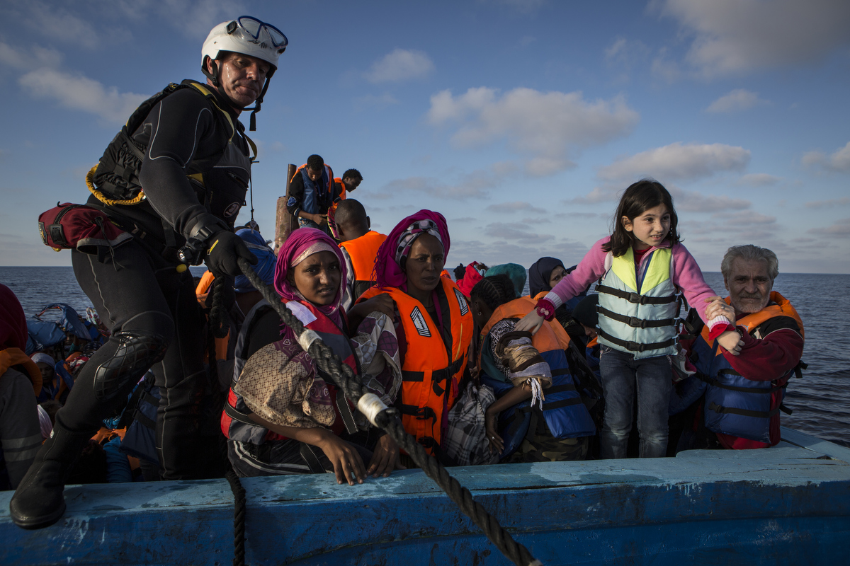 Rescue swimmer Jim onboard with Syrian and Eritrean migrants.