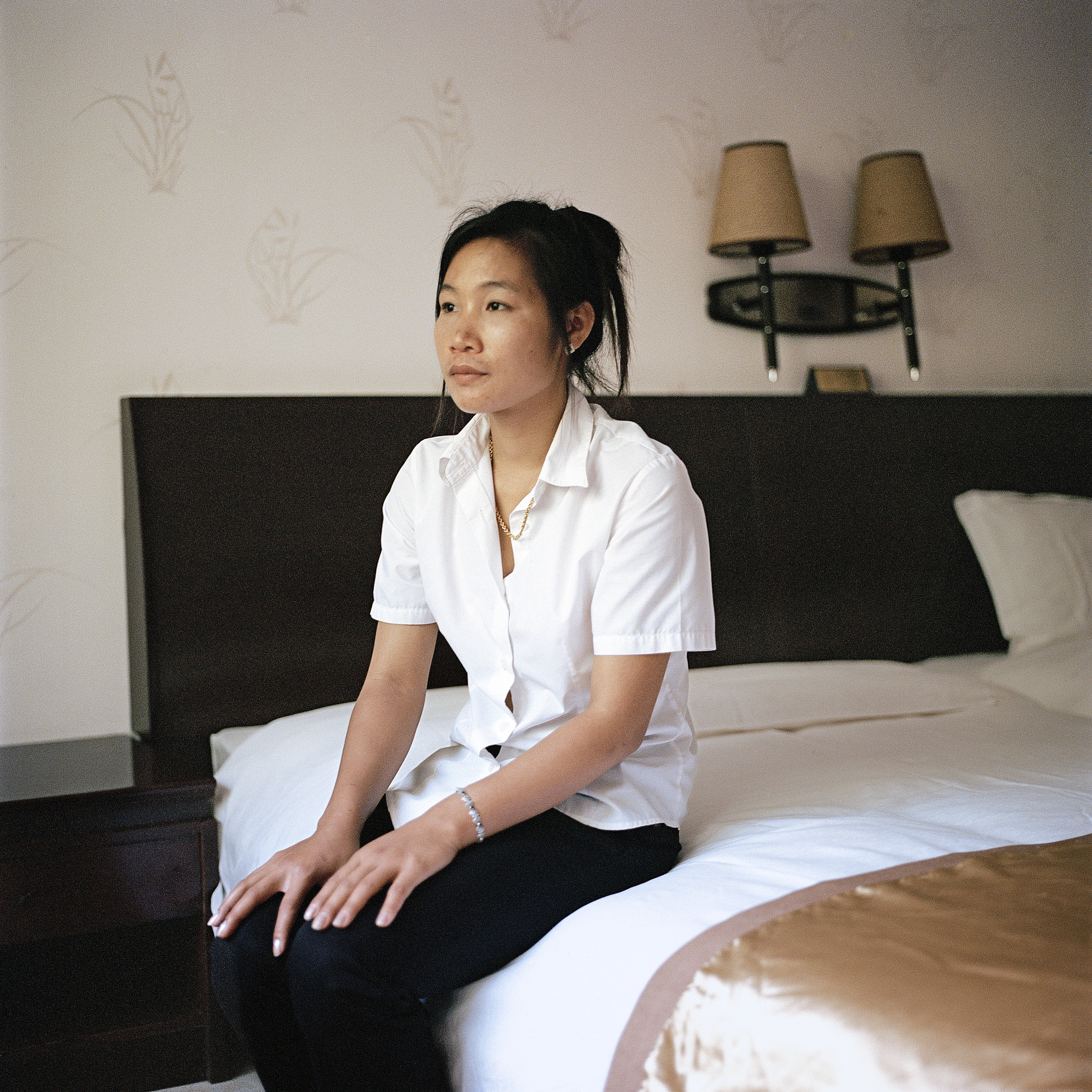 1. Hotel operator Wei Qixing, from Fujian in China, owns a hotel in the Golden City. Once a brisk business, his hotel is now vacant except for him and two of his employees. / 2. Miss Liang, a 22 year old from Luang Prabang, is one of the 12 housekeepers remaining in the Golden City Casino Hotel. At its peak, the hotel had 100 housekeepers, mostly from China.