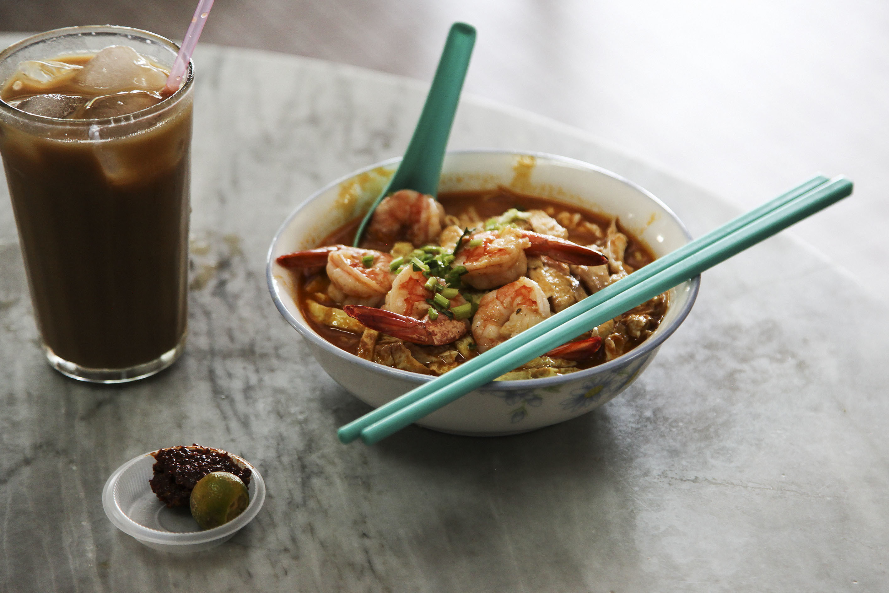 Bourdain eating Sarawak laksa at Choon Hui Cafe.
