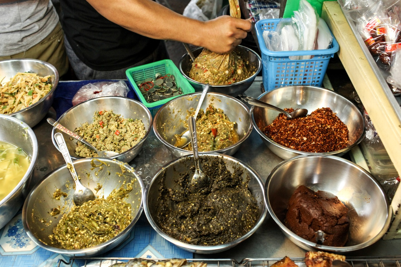 Five chili pastes at the market (clockwise from top center): nam prik sa mun pri (herb paste), nam prik kha (galangal paste), nam prik tha dang, and two versions of nam prik num.
