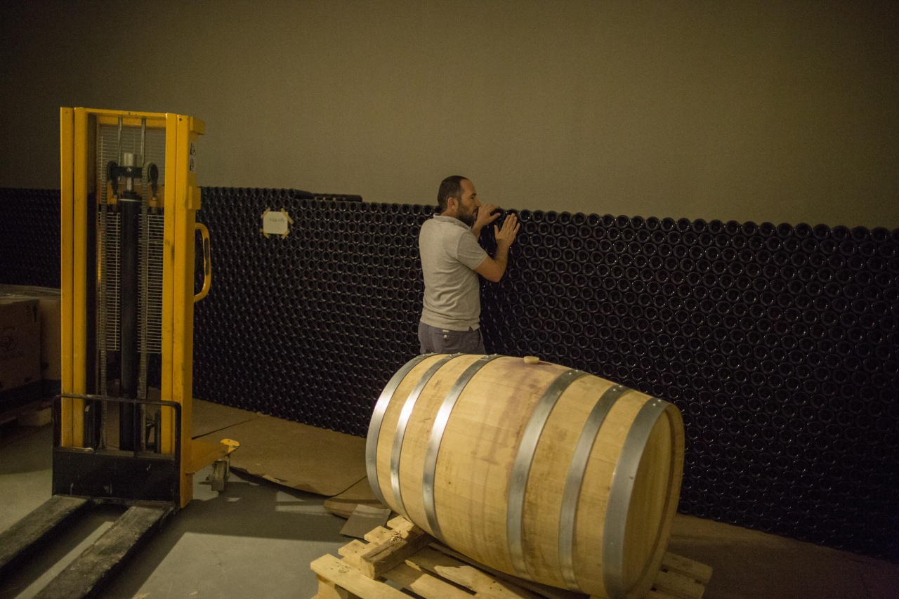 Walid Habshi, a farmer, member of the Heliopolis Cooperative and co-founder/partner in Couvent Rouge, inspects bottled wine in a huge cellar in the basement of the Couvent Rouge winery.