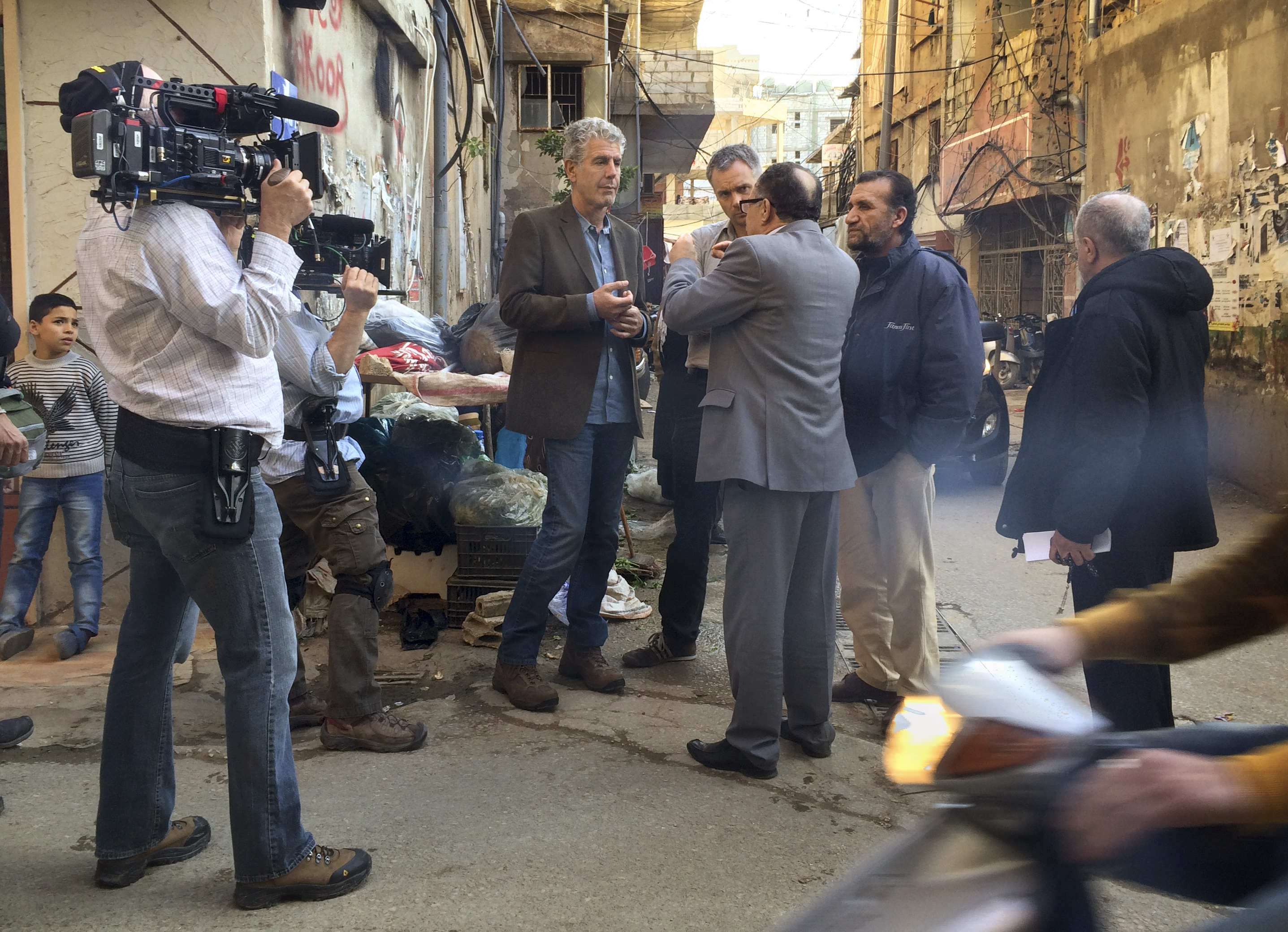 Bourdain and Nick Patton Walsh (to Bourdain's immediate left) speak with Mr. Najem (back to camera).