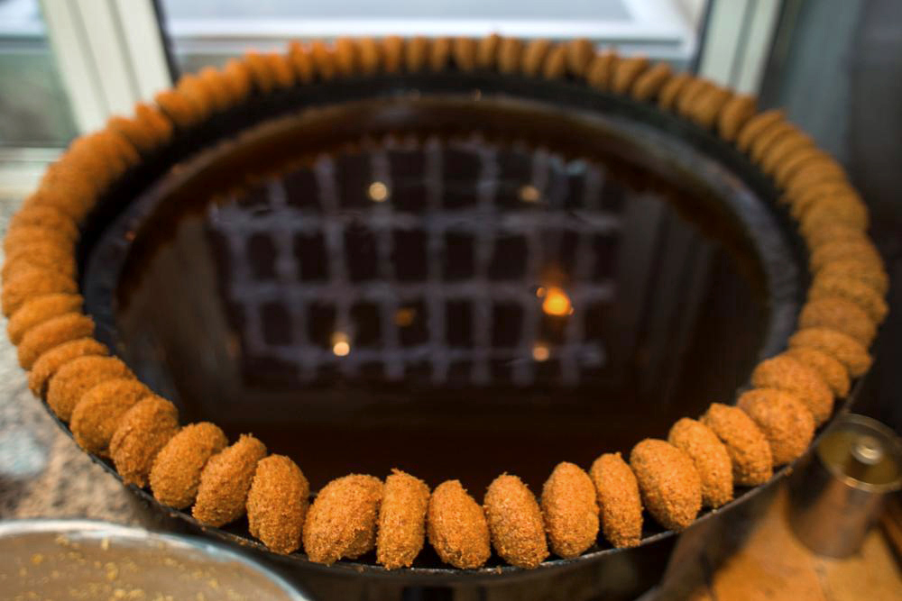 A ring of freshly fried falafel. The building across the street, reflected in the falafel oil, was gutted during the civil war and has never been rebuilt.