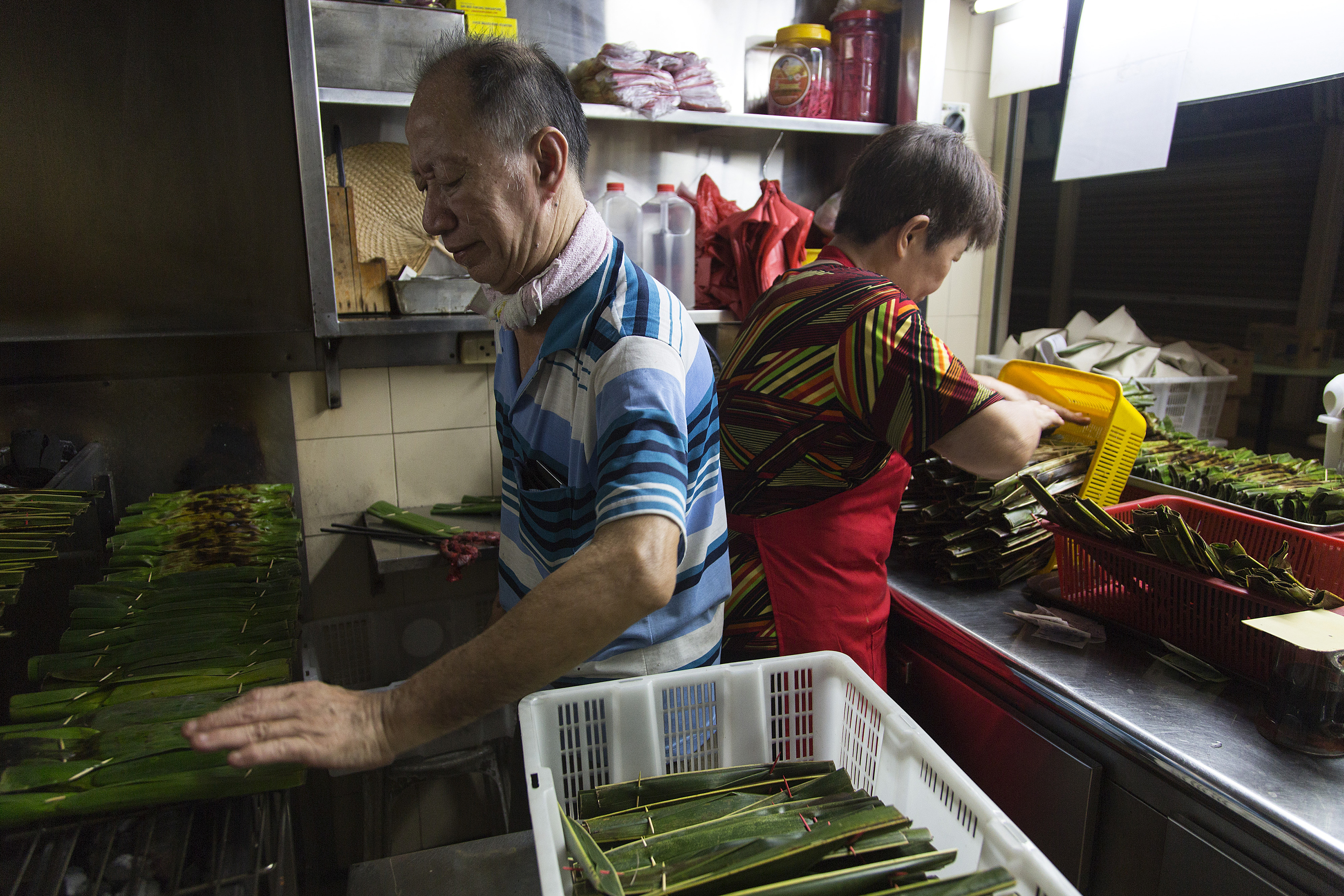 Tan Beng and Tee Ai Geok prepare otah in their stall at Old Airport Road Food Centre.