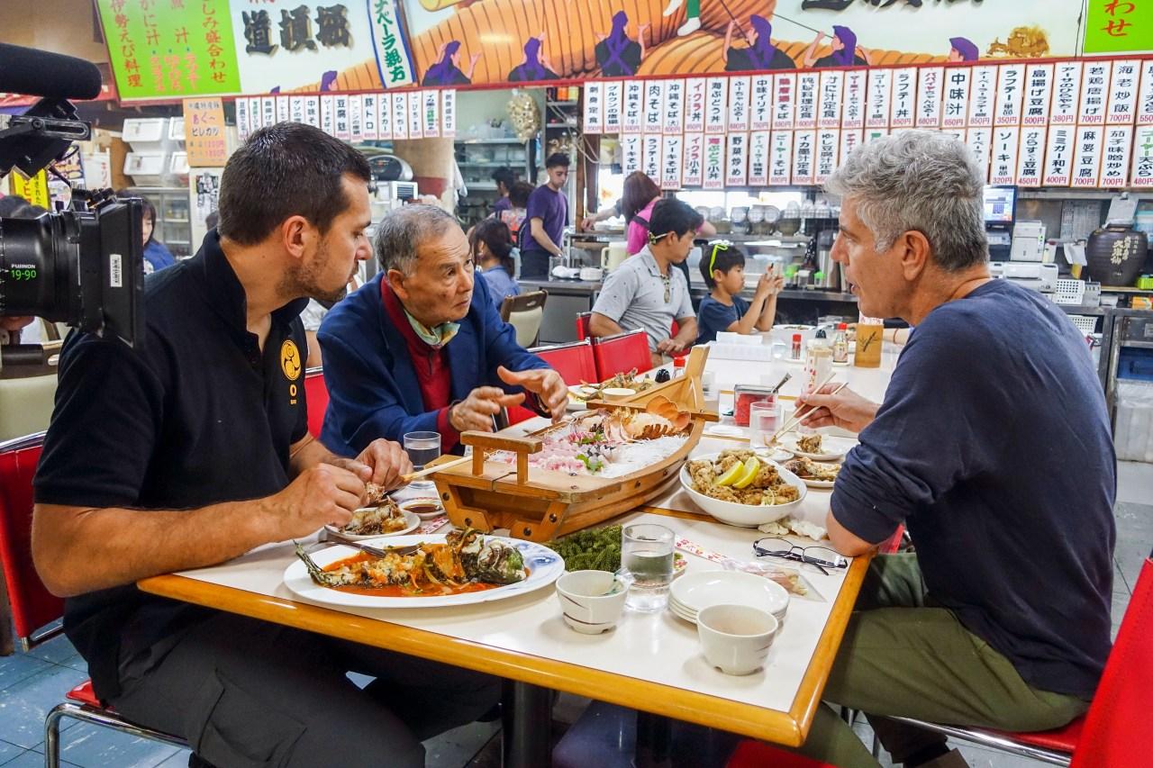 Bourdain eats with Master Hokama Tetsuhiro (middle) and black belt/translator James Pankiewicz (left) at Makishi Public Market in Naha, Okinawa.