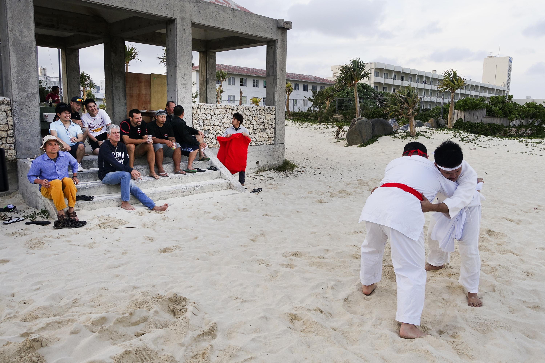 Bourdain watches Tegumi practice (Okinawan sumo wrestling) on Kume Island.
