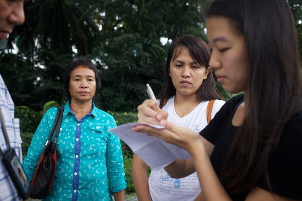 Jading's mother and sister looking on as an anti-death penalty activist writes down everyone's particulars for the security officer while submitting a personal letter of appeal to the President of Singapore to show mercy to Jabing.