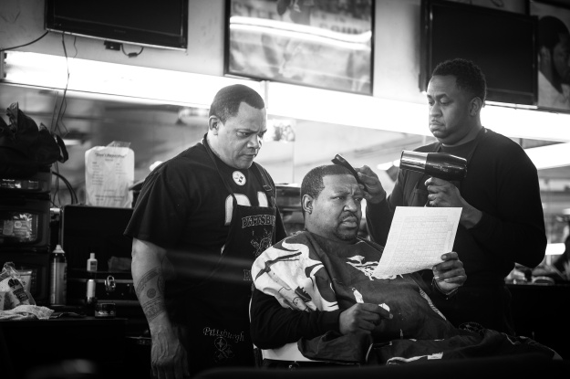"1. Reggie ""Feeny"" Ward Jr. reads a football poll to barbers Kevin Adams and Edward Azeem. Feeny was a regular customer until he passed away a few months ago. / 2. Joseph Cook waits for a ride outside of Dave's Barber Shop after getting his hair cut."