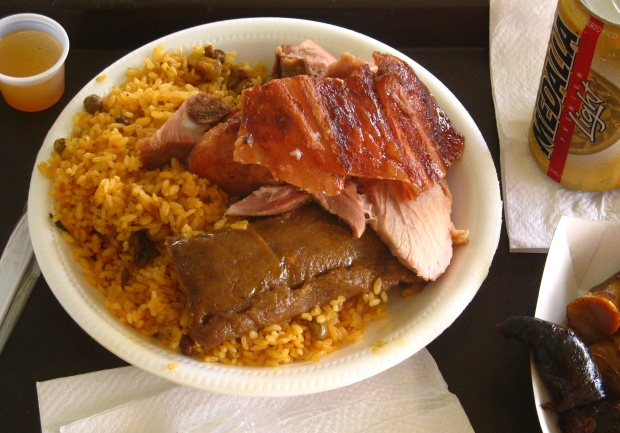 Lechon served with plantain tamal, rice, pork sausage, and blood sausage. (Photo by sfchef via flickr.com)