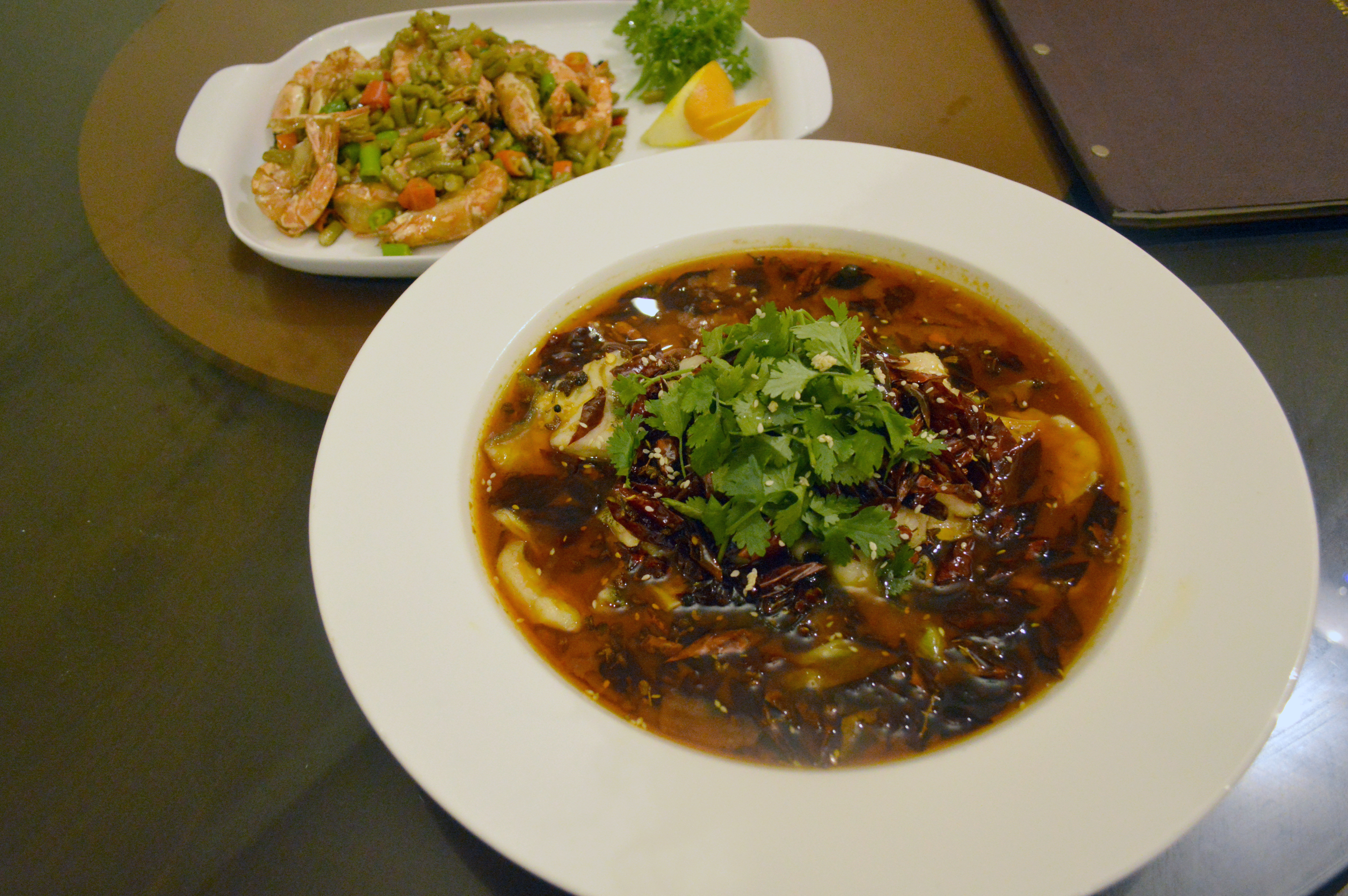 1. A plate of steamed and deep-fried mantou bread served with condensed milk. / 2. (In the foreground) Shui zhu yu or boiled fish fillets in hot chilli oil is a Sichuan speciality. The hot oil with Sichuan peppers and dried chillies poured over the fish lends it flavor, fragrance and a slow burn. In the background is a simple dish of prawns tossed with French beans and chillies.