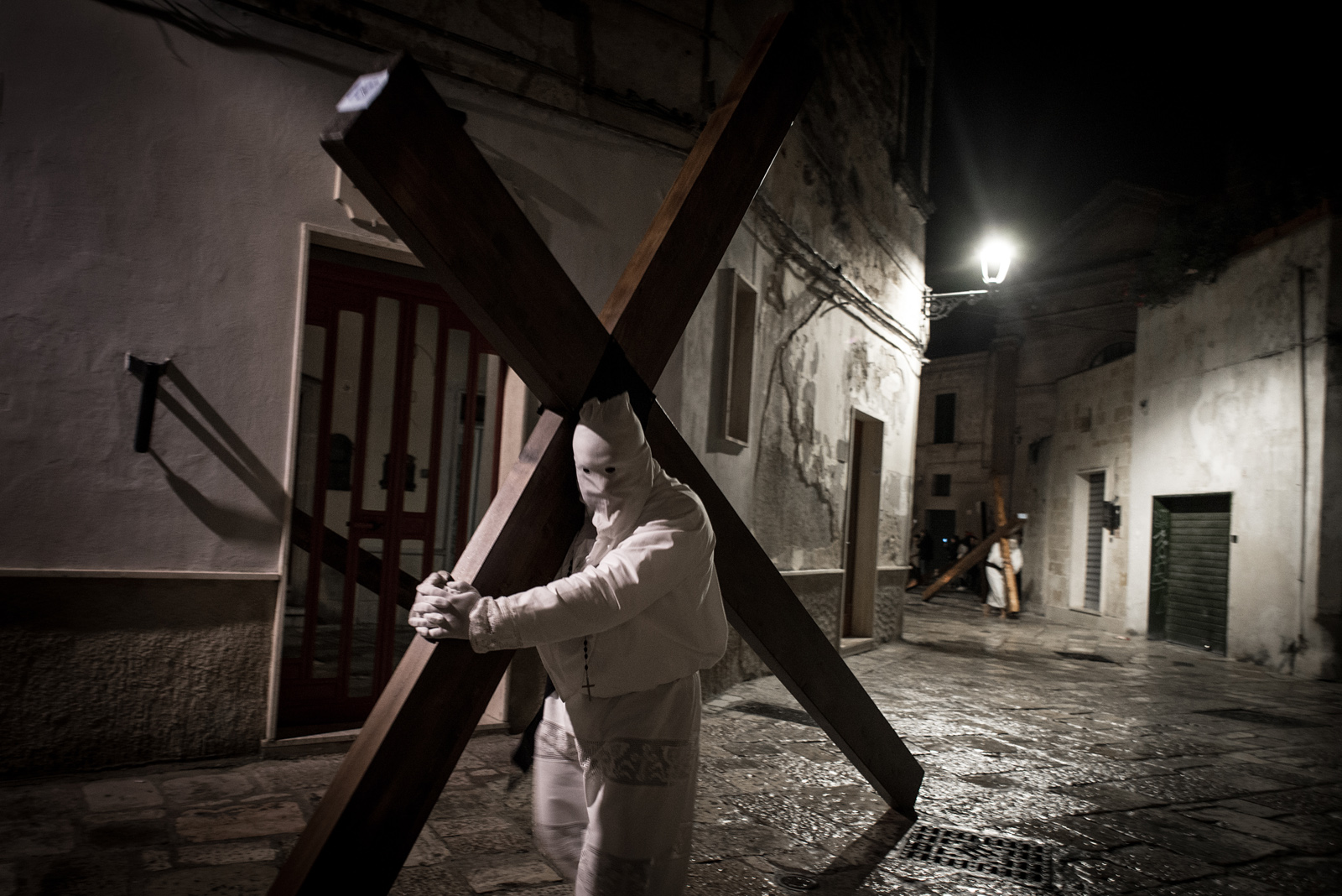 "1. Two ""Pappamusci"" worshippers in a church during the Holy Week pilgrimage in Francavilla Fontana. Pairs of barefoot penitents dressed in white visit all of the churches in the city throughout the night to ask for forgiveness from the Lord. Their identity is kept strictly secret. / 2. In Noicattaro, Molfetta, Francavilla Fontana and other cities of Apulia, hooded penitents called ""Cruciferi"" drag crosses along the streets in procession."