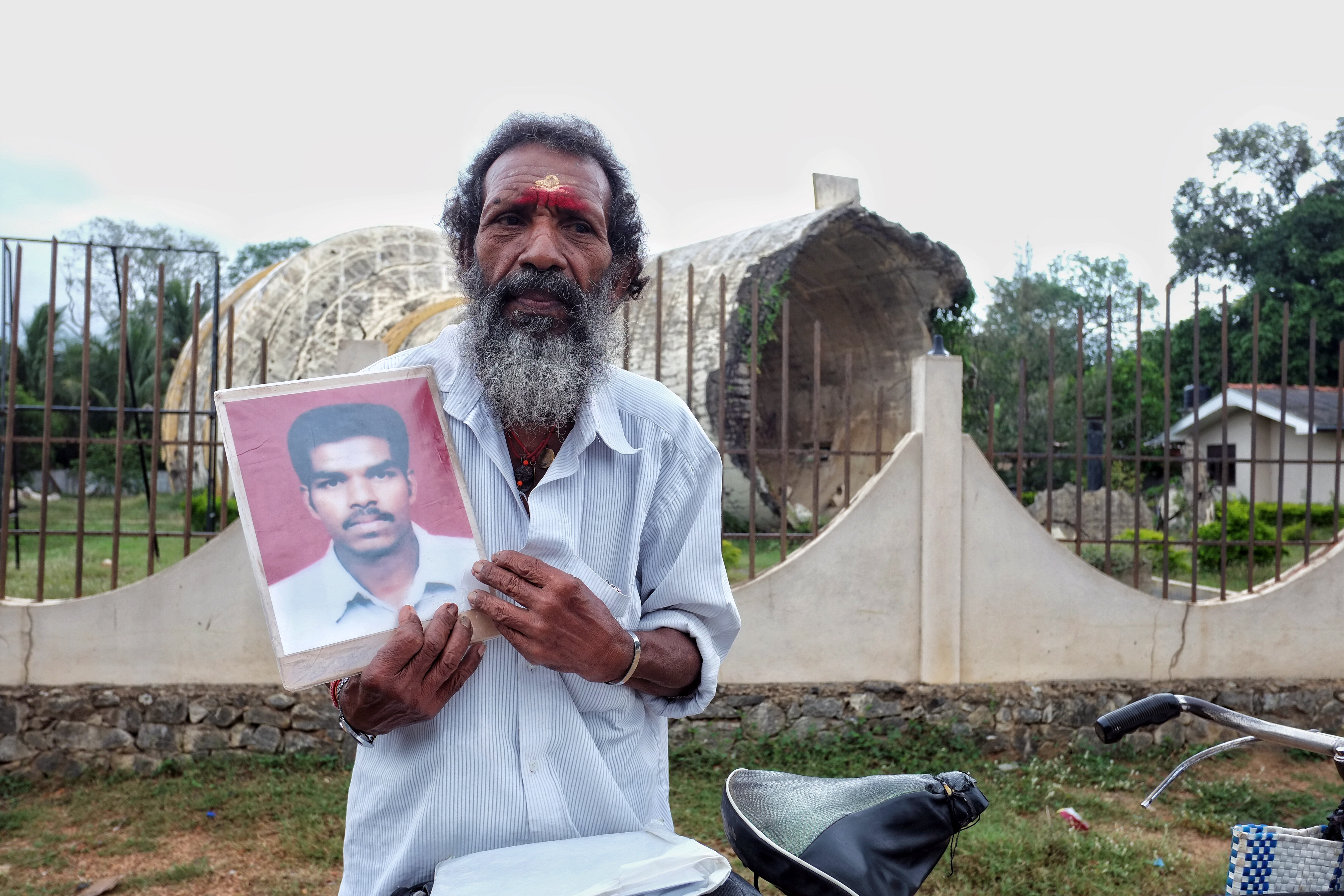 Muddan Thavendran shows a portrait of his son, who has been missing since 2008.