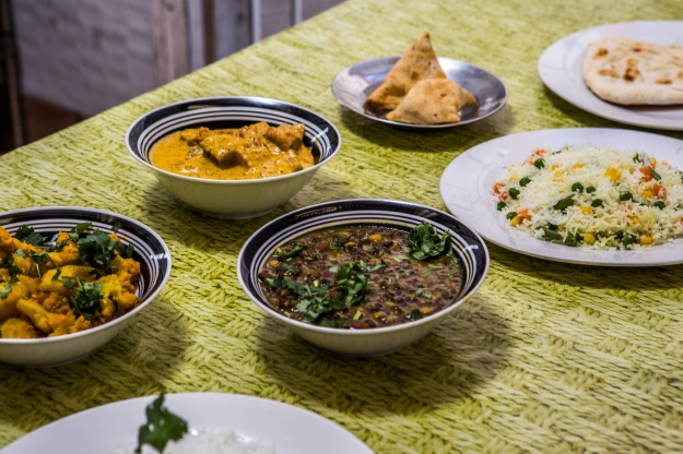 A selection of what's on the menu at Masala Cuisine: samosas, masala chicken, aloo gobi, and rice.