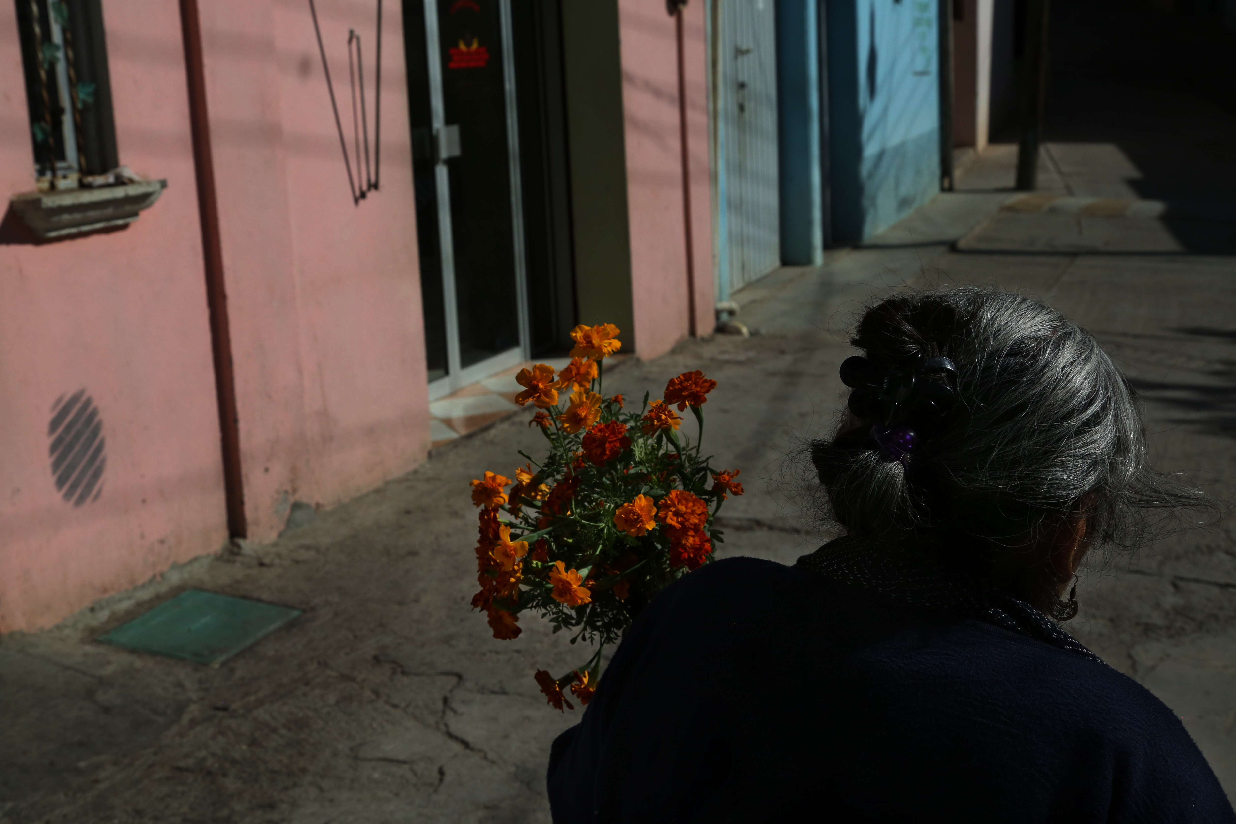 Photo 1: Teresa Raymundo walks to a funeral with a bundle of flowers in San Juan del Rio, Oaxaca, Mexico. Photo 2: The church in San Juan del Rio, Oaxaca, Mexico was built in the early 1800's.