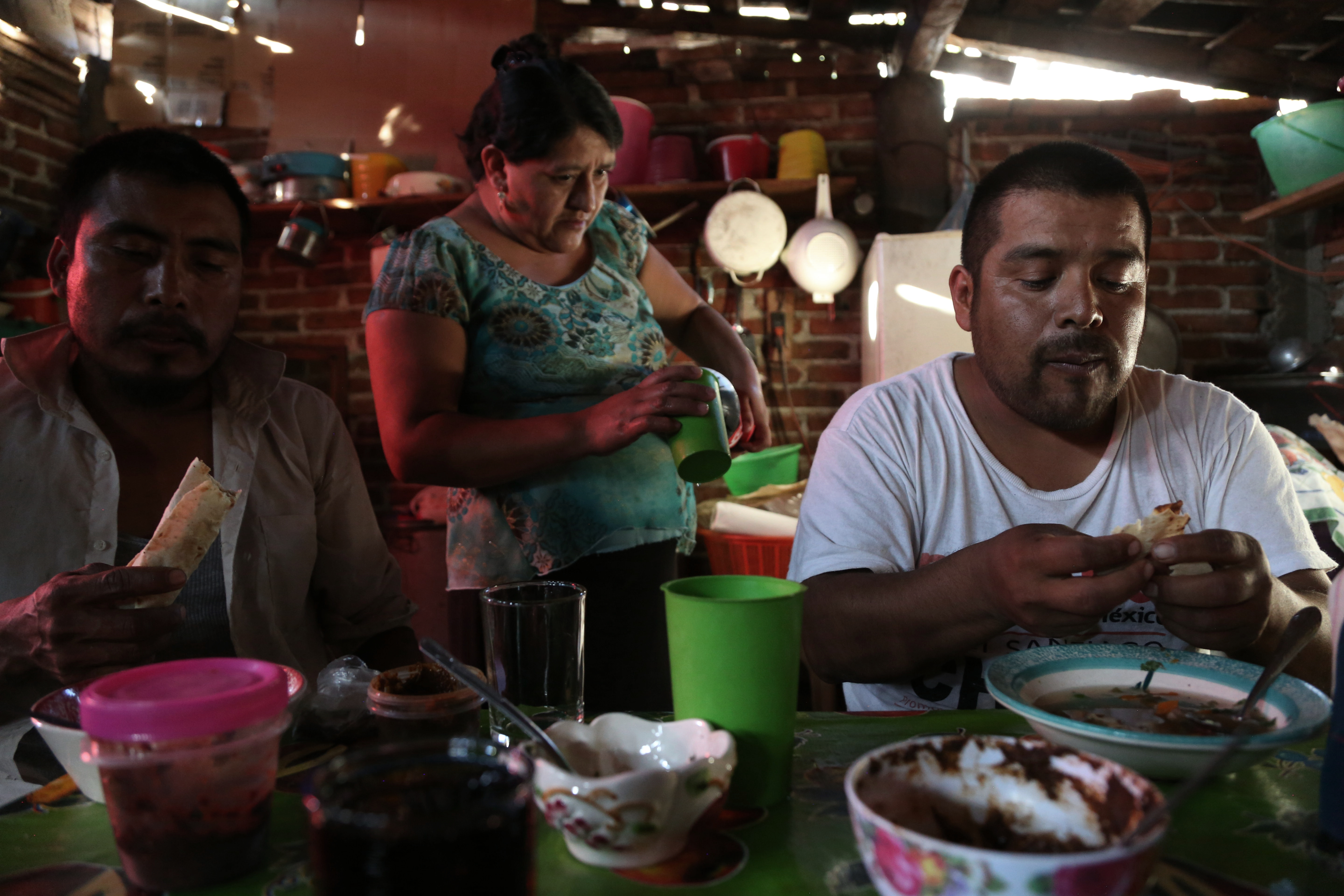 Fortunato Angeles and his brother-in-law, Raul Marin, eat pozole and fresh tortillas after a day at the palenque in San Juan del Rio, Oaxaca.