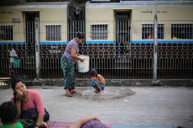 1. Children nap during the day's heat on a mattress between the station's wooden benches. / 2. A mother bathes her son at the station. One of the benefits of living at the station is running water.