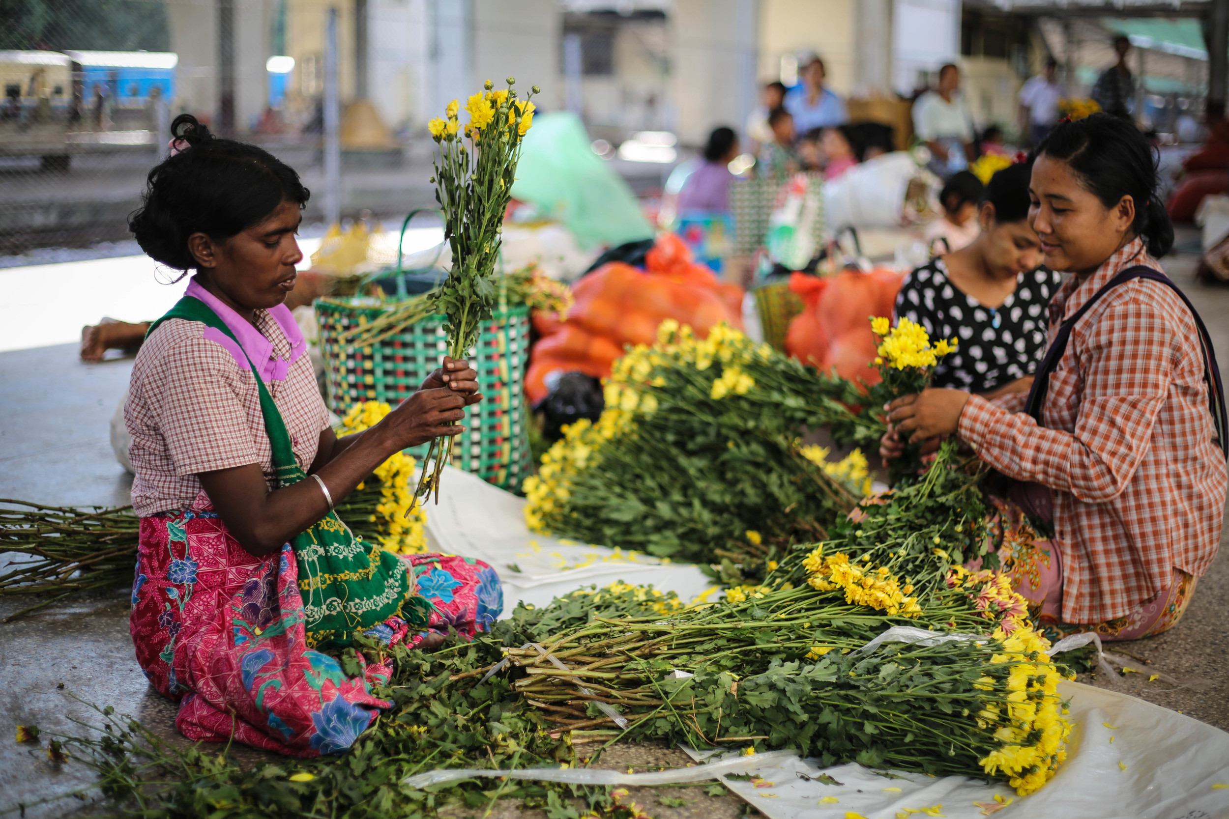 1. The station's ill­-equipped security guards, police, and workers often also live at the station as part of their benefits./ 2. Women sort through fresh flowers that had just arrived at the station in the early morning.