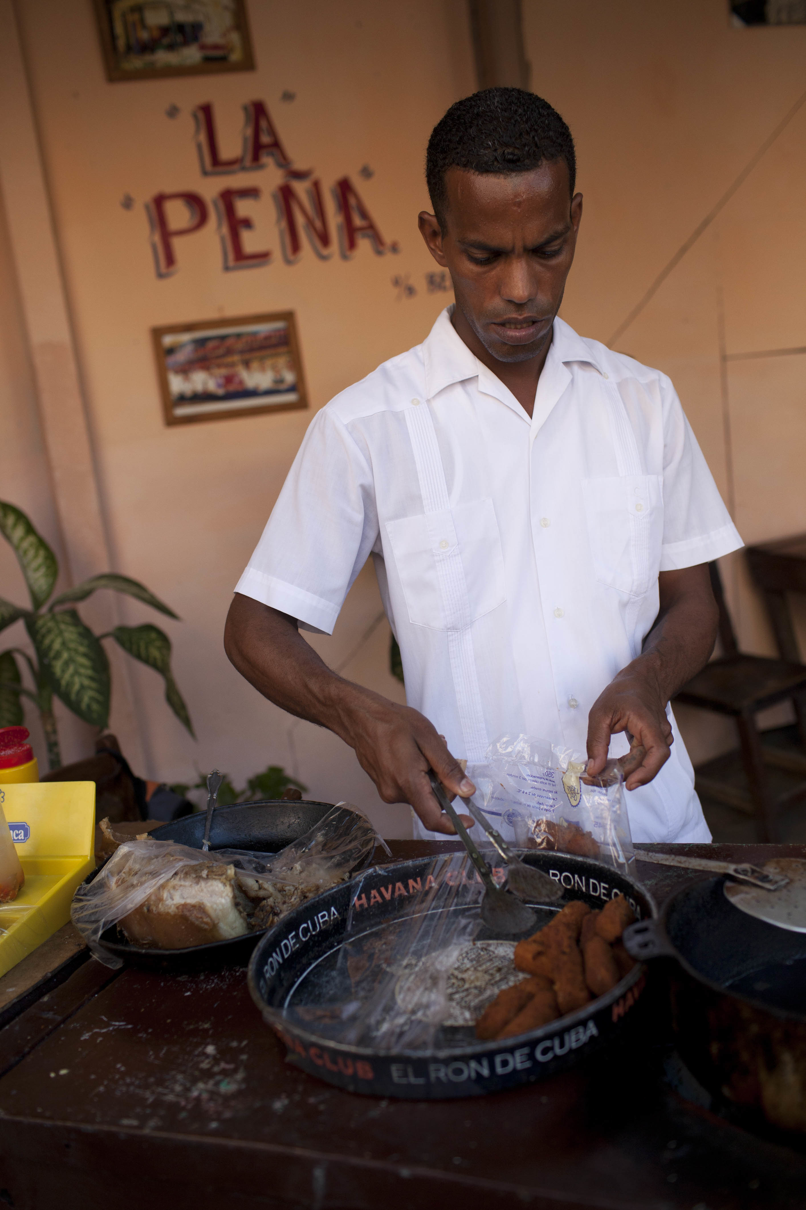 A Cuban man serves croquettes from a tray in a small local cafe, Havana old town. (Photo by In Pictures Ltd./Corbis via Getty Images)
