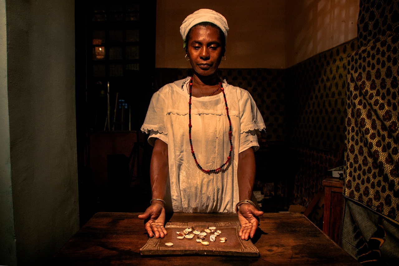 Mãe Marta stands above her divination instruments, the buzios or cowrie shells. As she tosses them on her table, the position in which they fall indicates a response from the Orishas, which she interprets for the inquirer.