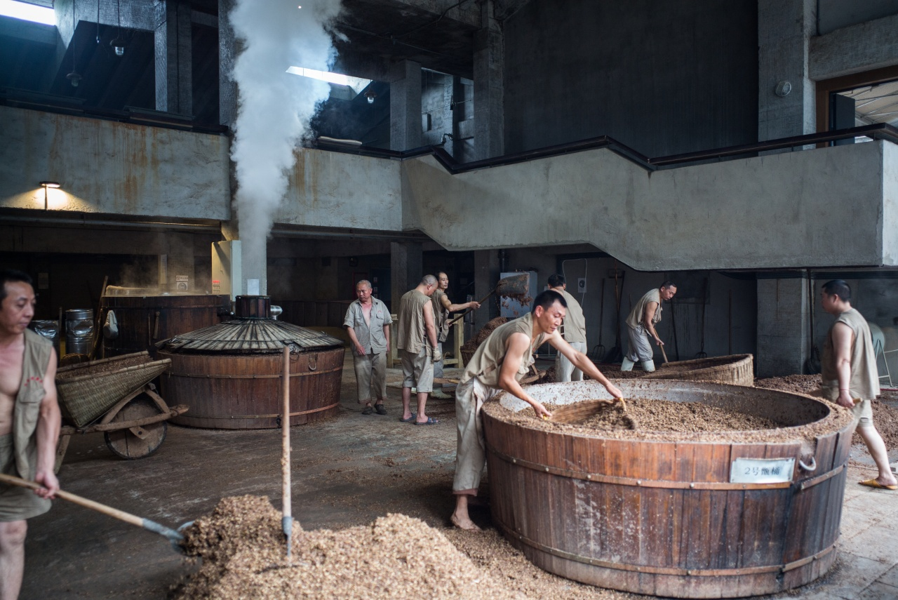 Workers fill vats with grain in preparation for alcohol production at the baijiu production demonstration area at the Shui Jing Fang Museum in Chengdu, China.
