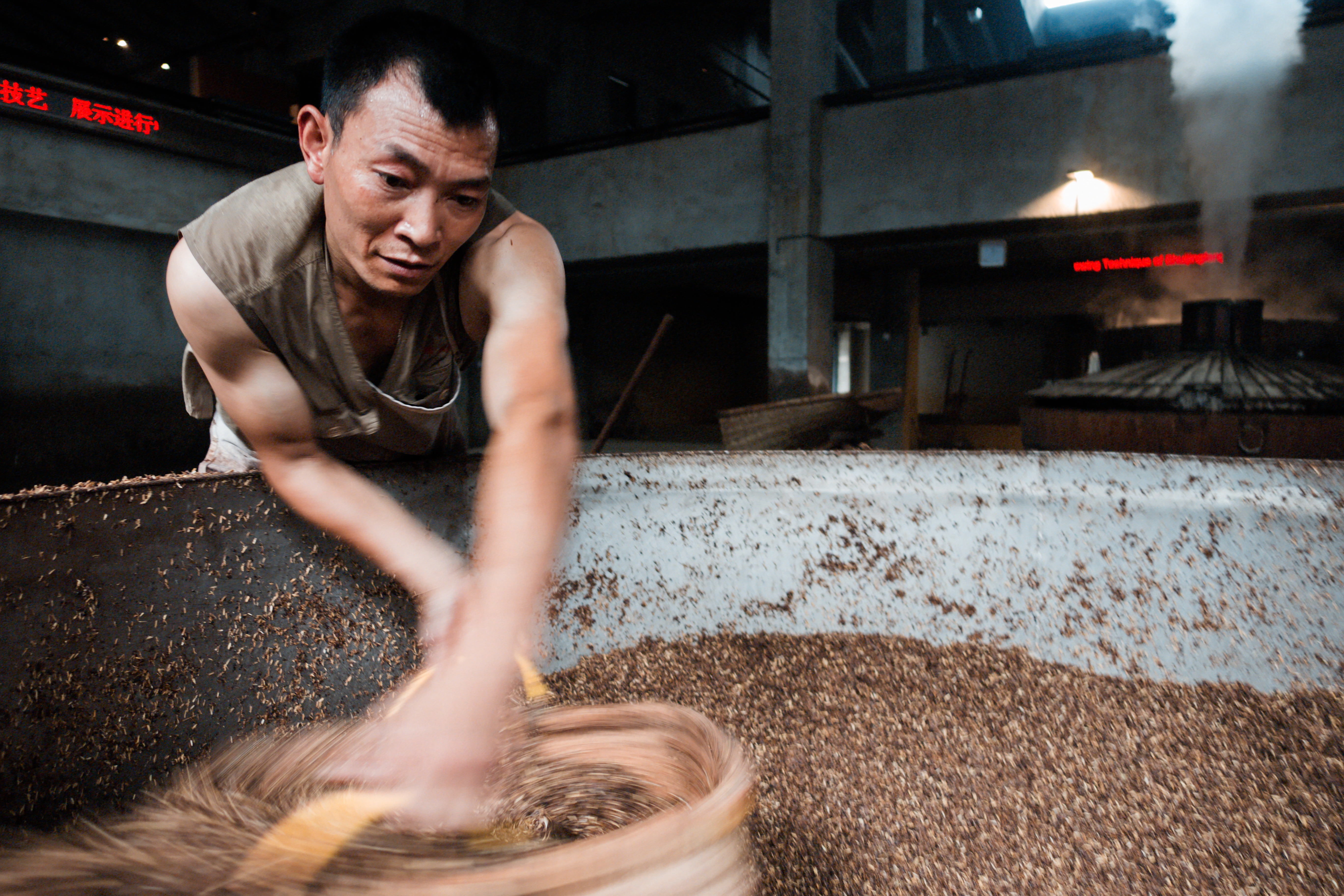 Photo 1: A worker sifts through a vat of grains at the museum production area. The museum is dedicated to the history and culture of this quintessential Chinese spirit. Photo 2: Workers add Qu, or starter culture, to a mash of grains at the museum production area. Baijiu recipes vary widely and include grains like sorghum, rice, corn and wheat.