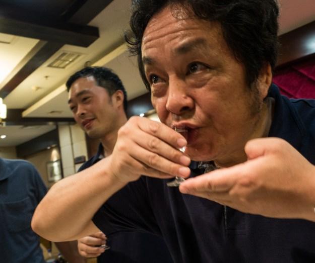 Photo 1: A snake flavored baijiu stands behind the bar at Capital Spirits. Photo 2: At a restaurant in Chengdu a worker prepares to down a shot of baijiu.