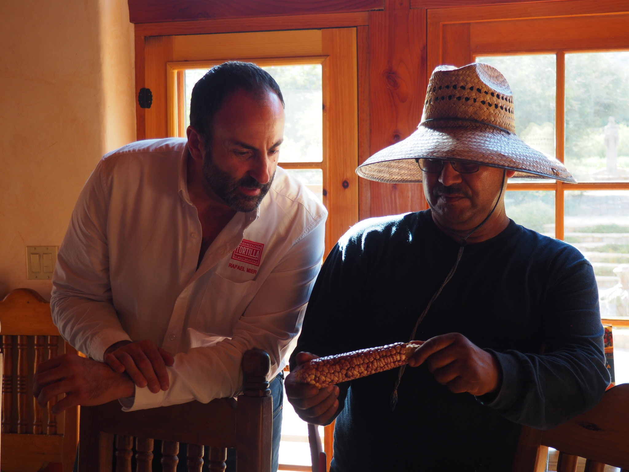 Rafael Mier showing an ear of corn to Salvador, the head farmer at Rancho la Puerta in Tecate, Mexico. (Photo by Jackie Bryant)