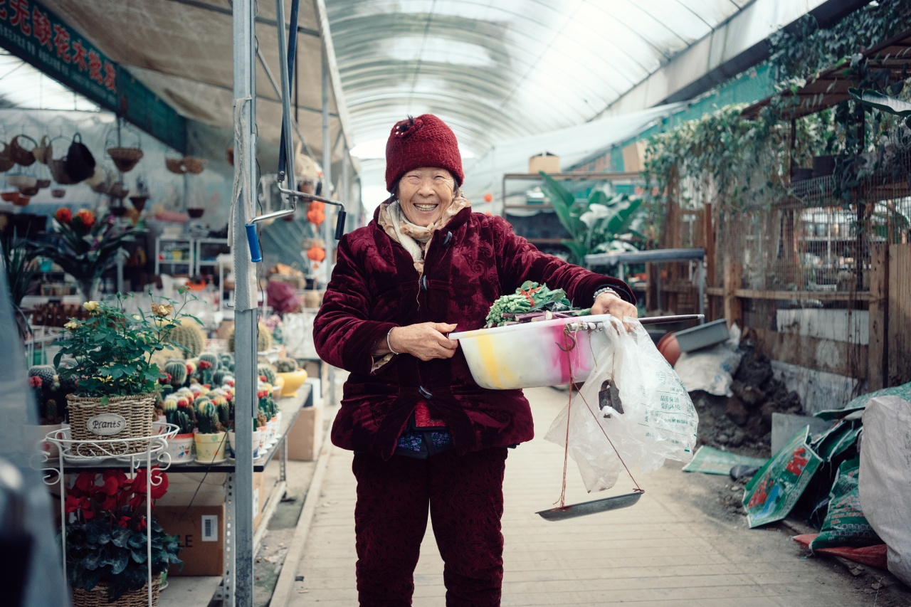 Mao, 79, sells her home grown vegetables in the flower market of San Sheng Flower Town.