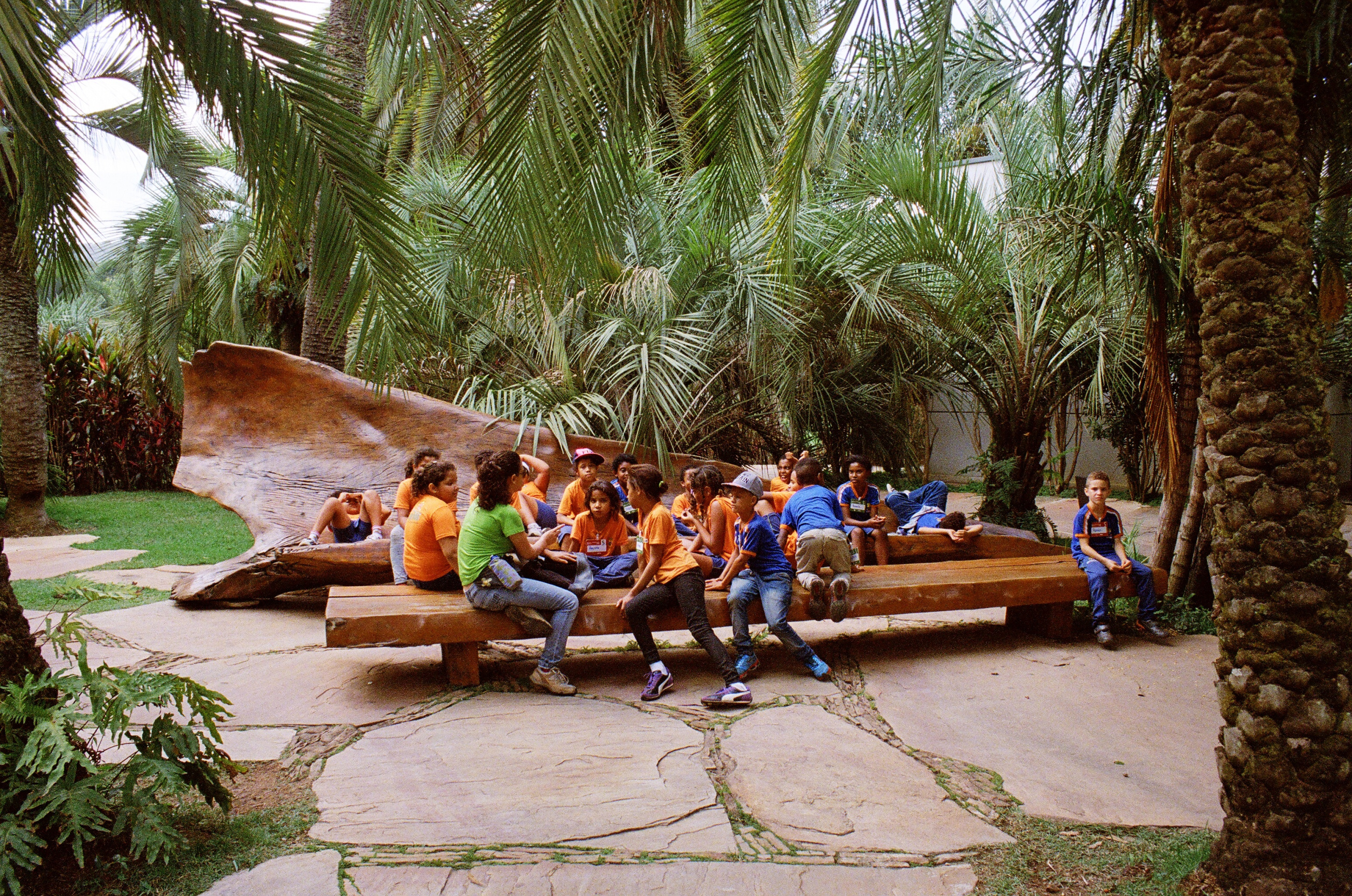 Local children from Inhotim's school outreach program gather on one of the park's trademark benches by Brazilian designer Hugo França.