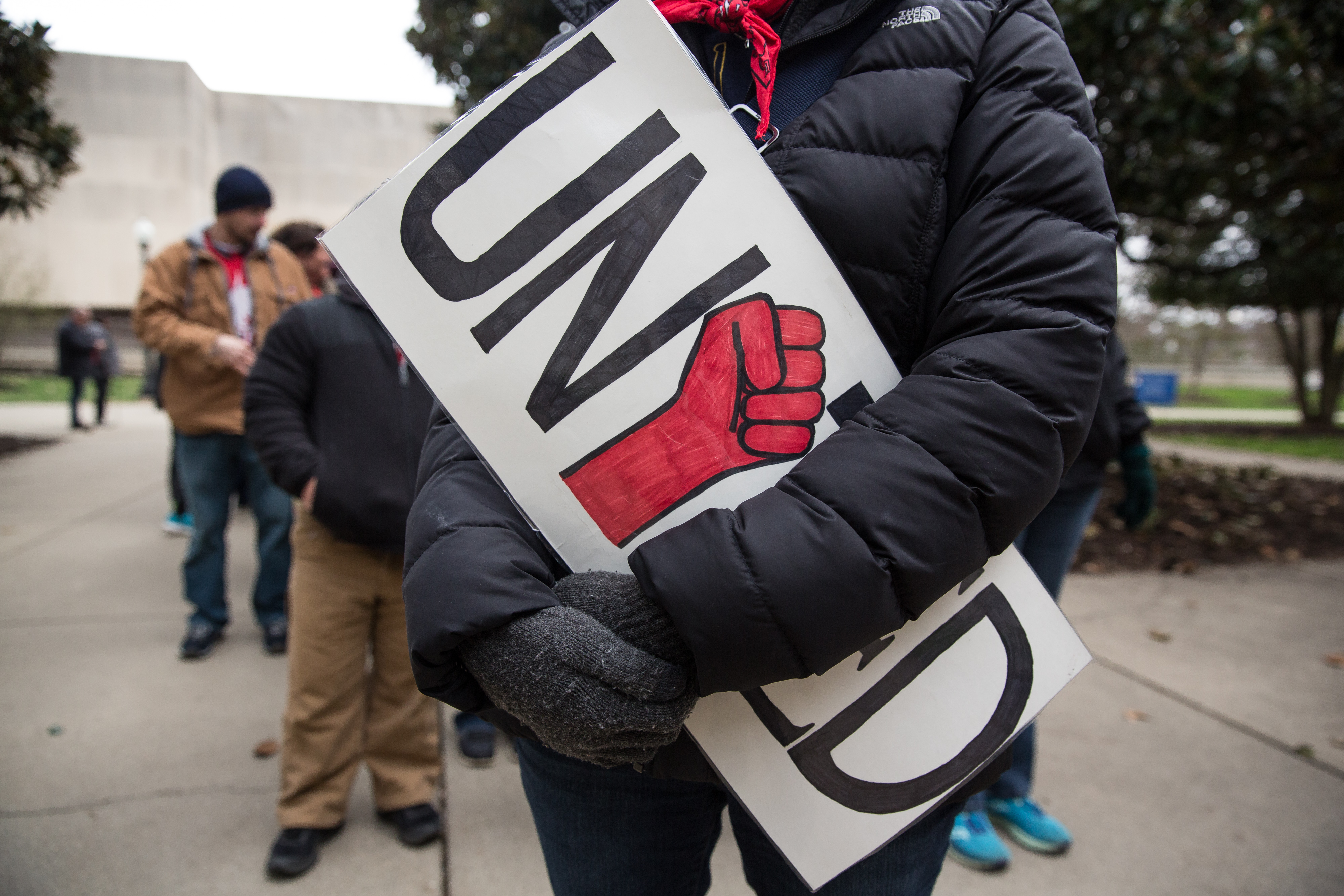 """A teacher held a """"United"""" sign during a rally outside the West Virginia Capitol in Charleston during a protest in March. Photo by Scott Heins/Bloomberg via Getty Images"""
