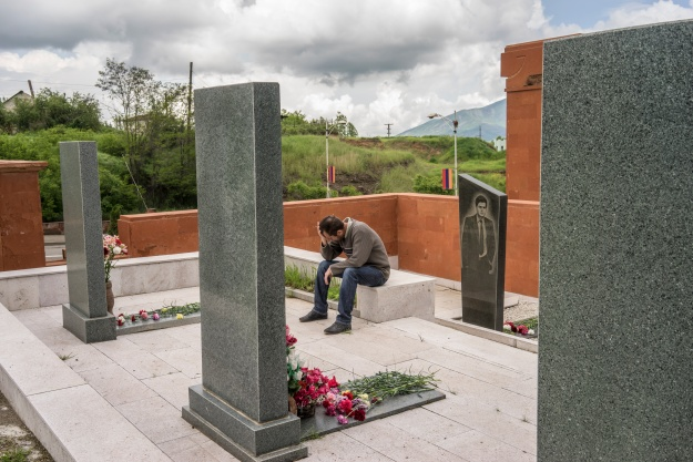 1. A man cries at the grave of a fighter killed in the 1990s war between Armenia and Azerbaijan. 2. Military officers wait for the start of the ceremony.