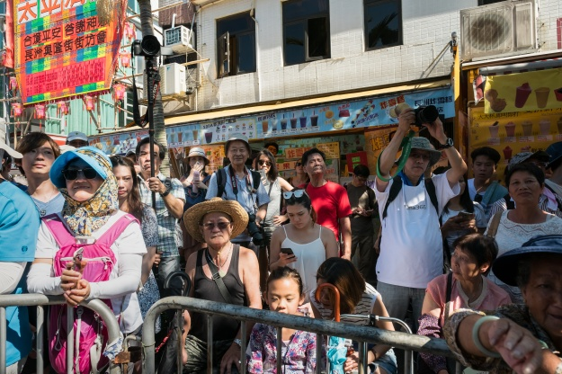 Visitors watch the Piu Sik (Floating Colors) Parade during the Bun Festival on Cheung Chau Island.