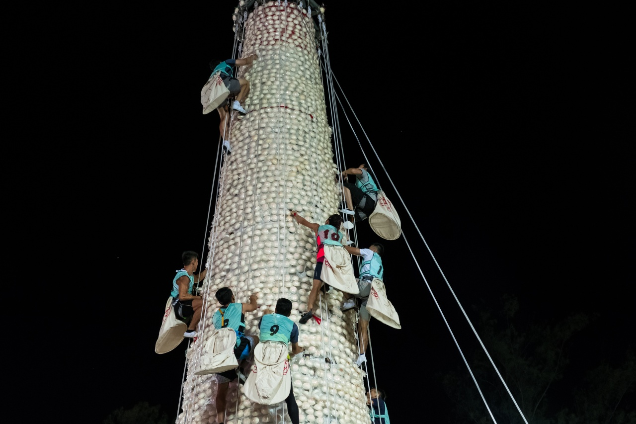 Angel Wong Ka-yan, #10, climbs the bun tower during the scrambling competition.