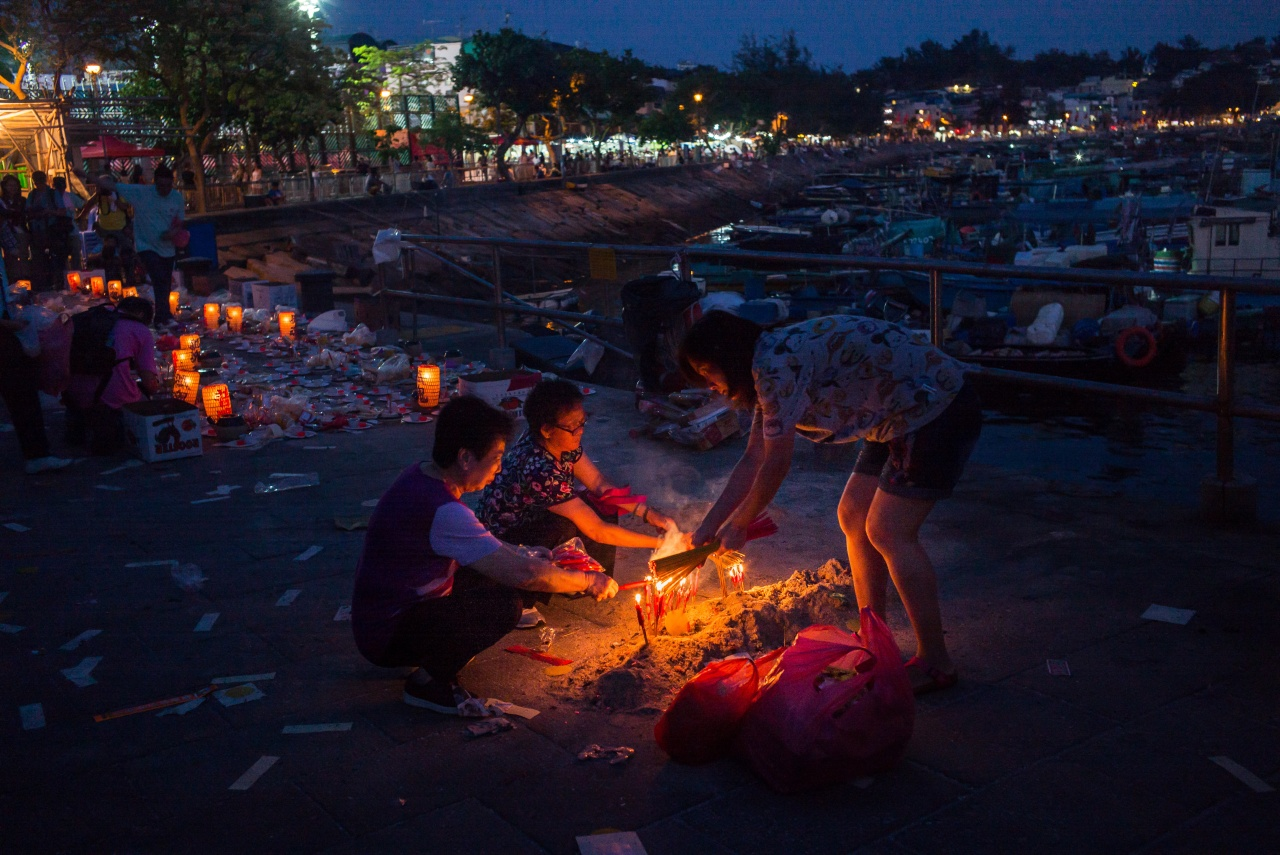 Women light incense near the paper effigy of the King of the Ghosts during the festival.