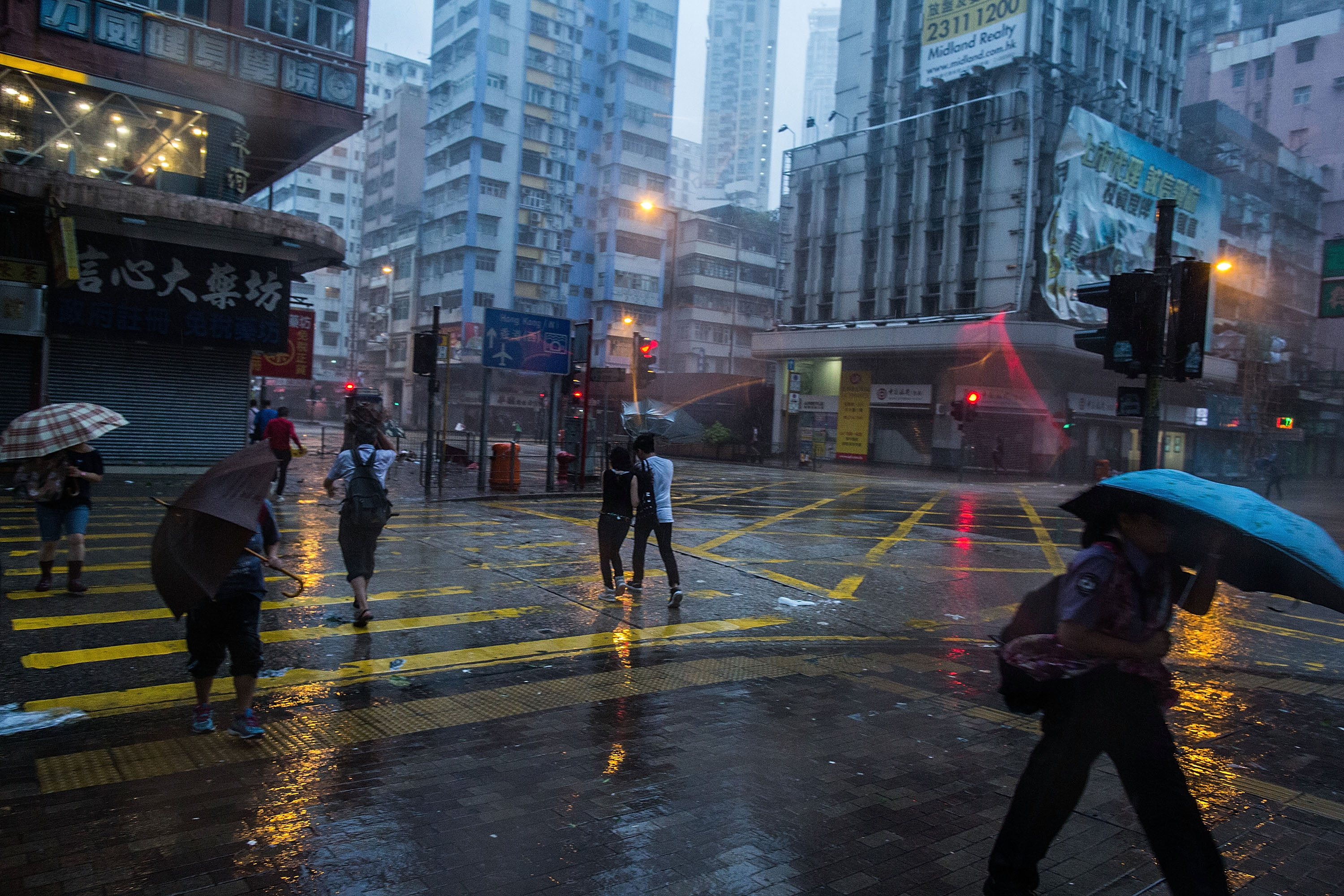 Pedestrians caught in high winds caused by a typhoon. Photo by Lam Yik Fei/Getty Images.