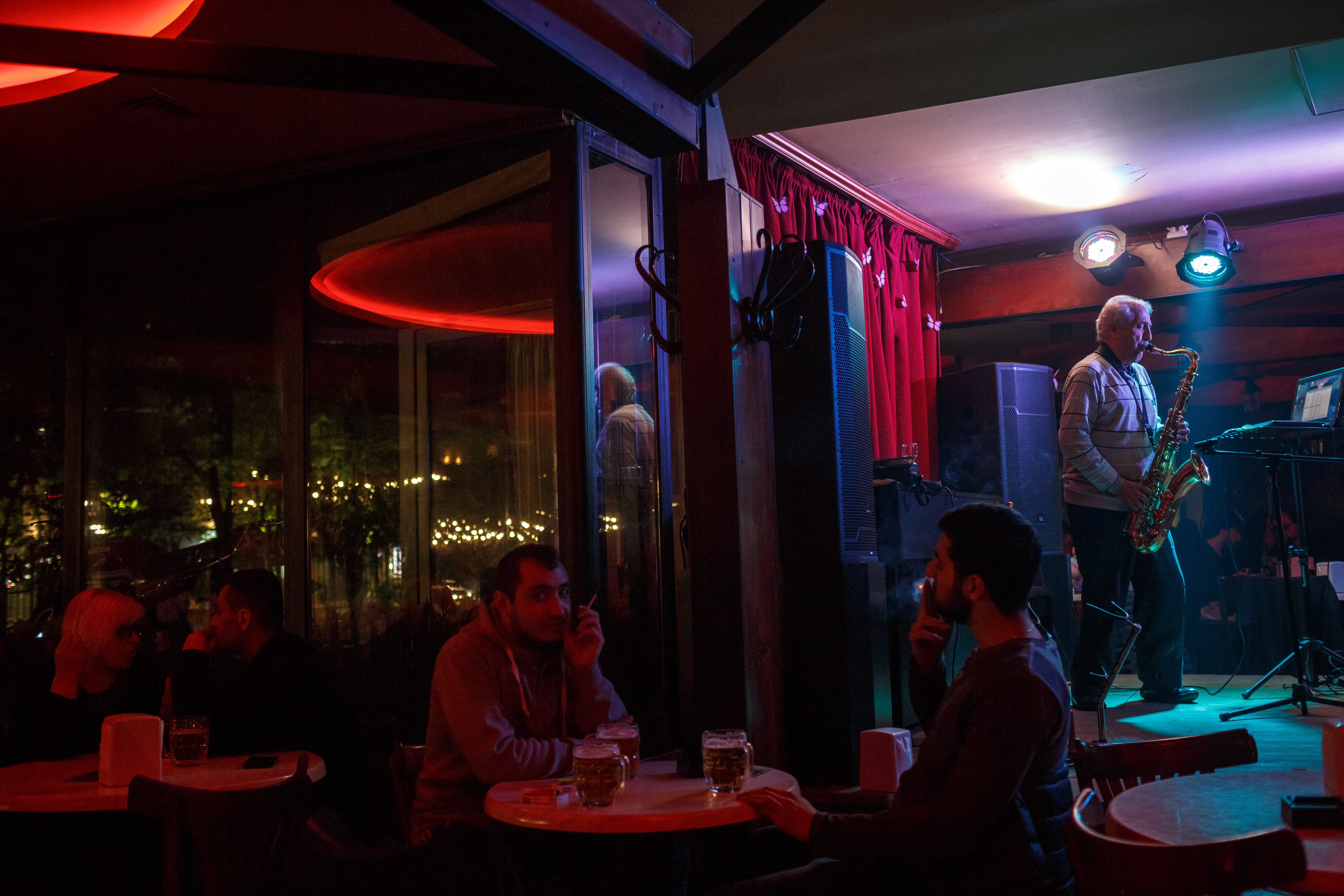A local musician plays the saxophone at a restaurant in Yerevan.