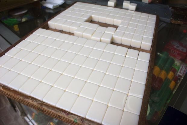 A tray of blank plastic mahjong tiles wait to be carved.