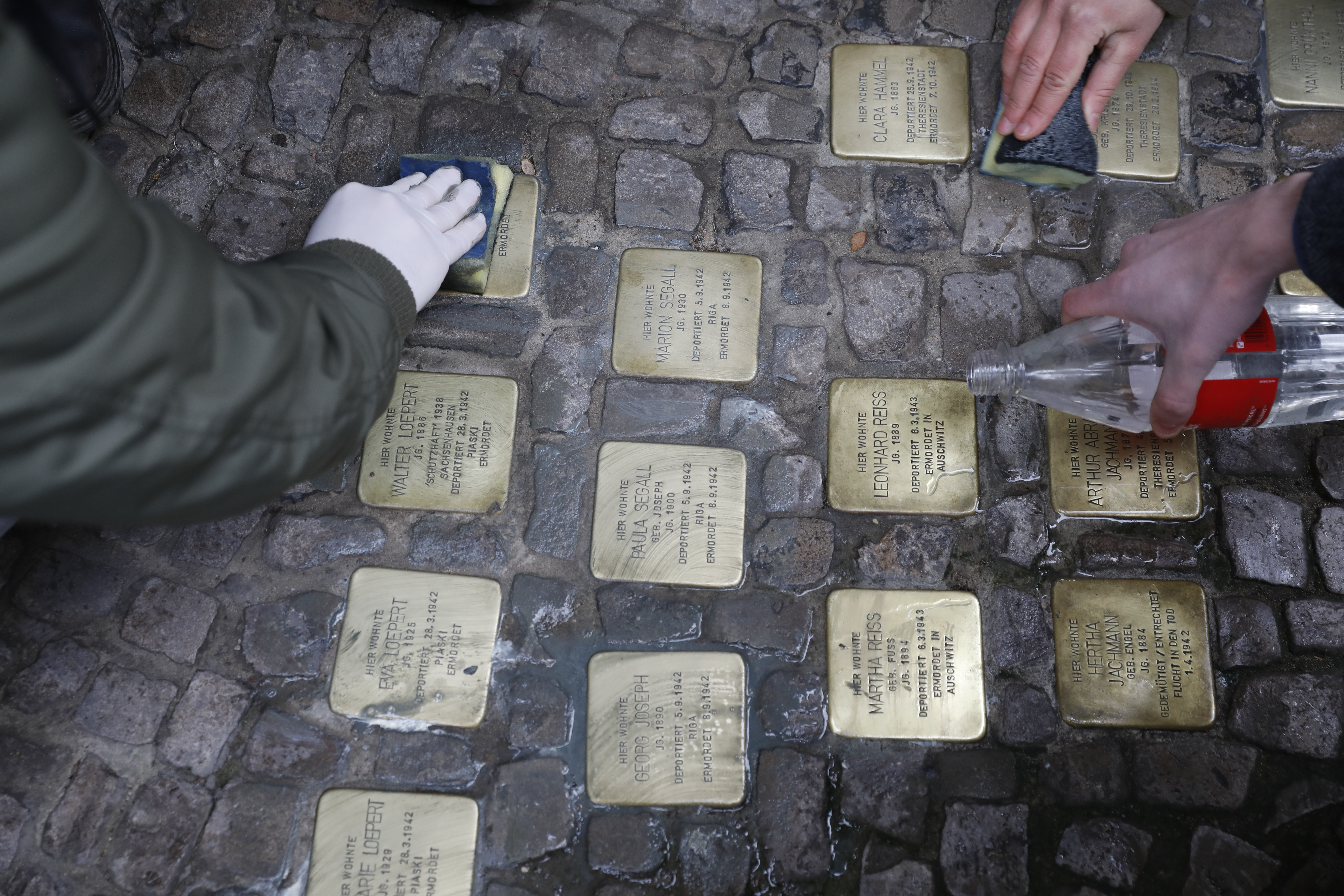 People clean the Stolpersteine memorials. Photo by Michele Tantussi via Getty Images.