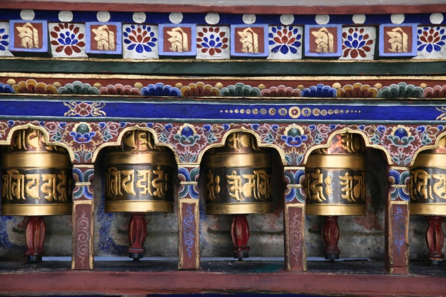 1: Painters touch up a temple in Paro. 2:  Buddhist prayer wheels at Kyichu Lhakhang Temple.
