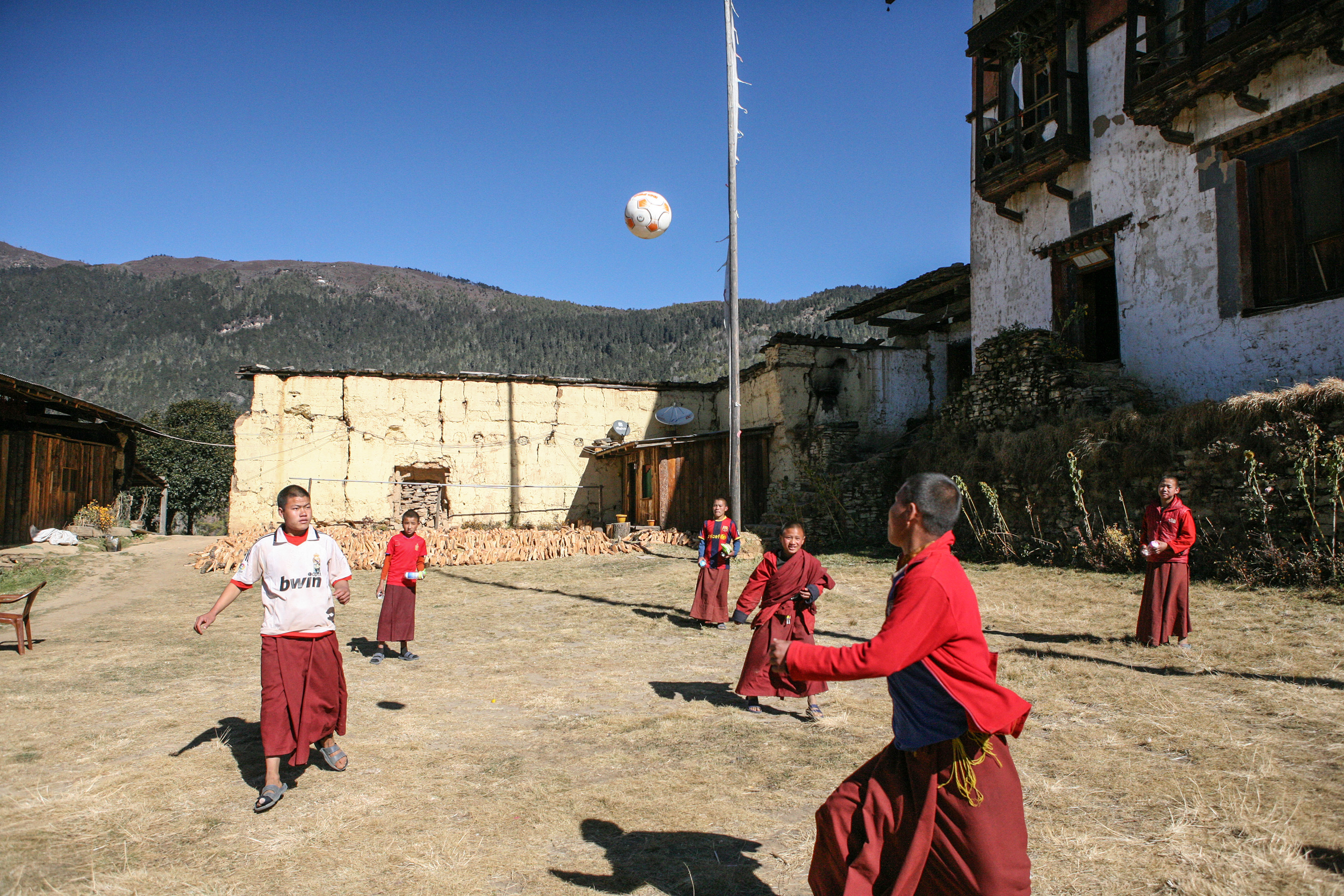 Monks take a break from their religious studies to play soccer in front of Nyepheu Monastery in Shaba, Paro Valley.